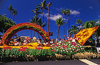 Aunties waving from a colorful float at the  aloha week parade in Waikiki along Kalakaua avenue