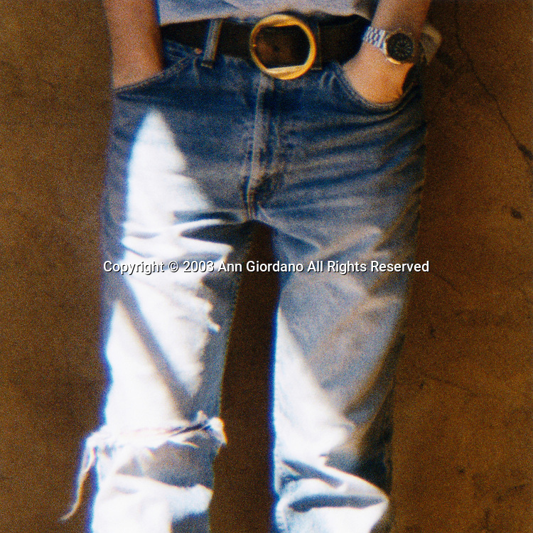 Waist to knee view of young man in jeans with hands in pocket
