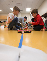 NWA Democrat-Gazette/BEN GOFF @NWABENGOFF<br /> Grayson Parrish (from left), 8, of Bentonville, Henry Woods, 10, of Rogers and Kingston Stone, 9, of Fayetteville construct a track for Hot Wheels cars from recycled materials Wednesday, March, 21, 2018, during the &quot;Wheels, Wings &amp; Motorized Things&quot; Spring Break camp at the Scott Family Amazeum in Bentonville. The camp, inspired by the museum's temporary exhibit Hot Wheels: Race to Win, gives campers hands on opportunities to explore elements of physics such as gravity, friction and momentum.