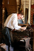 A blacksmith forges metal in the historic town of Williamsburg Virginia.