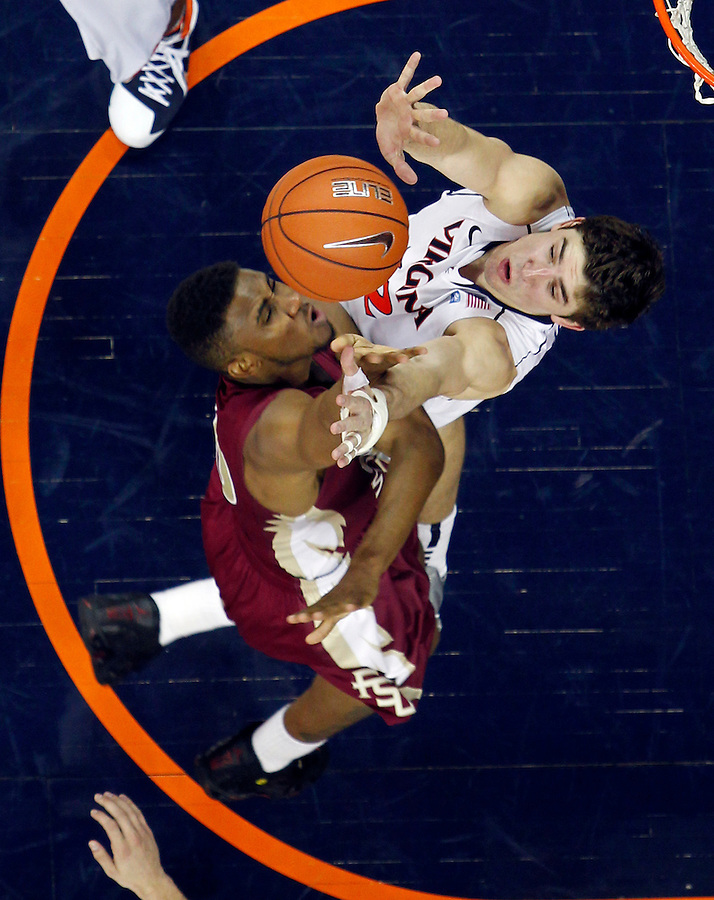 Florida State Seminoles guard Ian Miller (30) is defended by Virginia Cavaliers guard Joe Harris (12) during the game in Charlottesville, Va.  Florida State defeated Virginia 63-60.