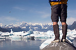 Alaska, Prince William Sound, Lone sea kayaker standing on glacial erratic, Columbia Bay, Columbia Glacier, pack ice, USA, North America, David Fox, released,.
