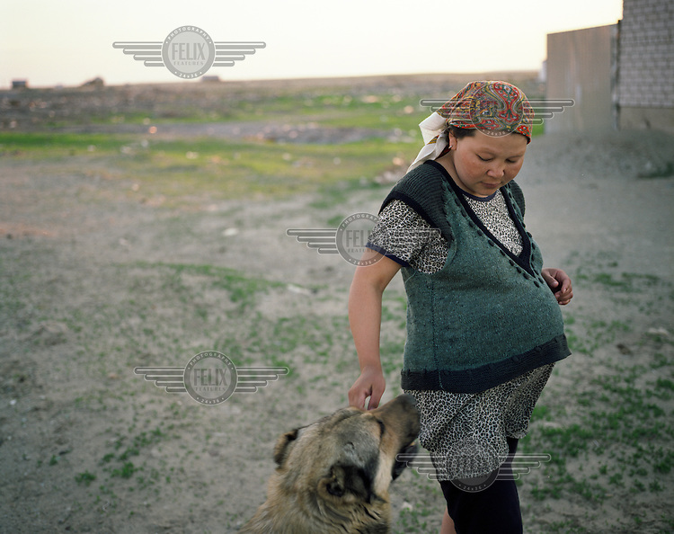 A pregnant woman strokes her dog as the sun fades in Aralsk.