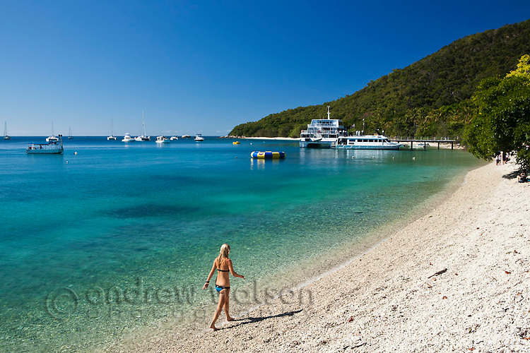 Woman walking along beach at Welcome Bay.  Fitzroy Island National Park, Cairns, Queensland, Austtralia