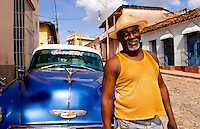 Portrait of local man in front of classic 50s blue Chevy  on streets of Trinidad Cuba