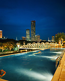 SINGAPORE, Asia, view of swimming pool at Fullerton hotel at night with the city in the background.
