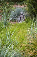 Statue accent focal point in California meadow garden with clipped green Moor grass (Sesleria autumnalis), and gray foliage wild rye (Leymus condensatus), David Fross