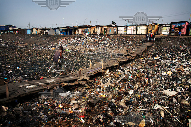 A man crosses a severely polluted river in the suburb of Agbogbloshie. When the rains come much of this waste will be washed to the sea. Agbogbloshie dump has become a dumping ground for computers and electronic waste from all over the developed world. Hundreds of tons of e-waste end up here every month. It is broken apart, and those components that can be sold on, are salvaged.