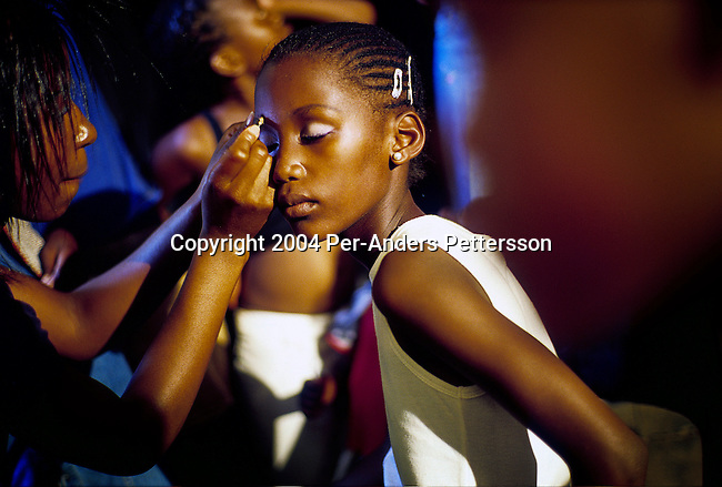 SOWETO, SOUTH AFRICA DECEMBER 20: An unidentified girl has her makeup up backstage before a beauty competition on December 20, 2004 in Soweto, Johannesburg, South Africa. The competition was part of a weeklong culture festival. Soweto is South Africa?s largest township and it was founded about one hundred years to make housing available for black people south west of downtown Johannesburg. The estimated population is between 2-3 million. Many key events during the Apartheid struggle unfolded here, and the most known is the student uprisings in June 1976, where thousands of students took to the streets to protest after being forced to study the Afrikaans language at school. Soweto today is a mix of old housing and newly constructed townhouses. A new hungry black middle-class is growing steadily. Most residents work in Johannesburg but the last years many shopping malls has been built, and people are starting to spend their money in Soweto.  .(Photo by Per-Anders Pettersson/Getty Images)..