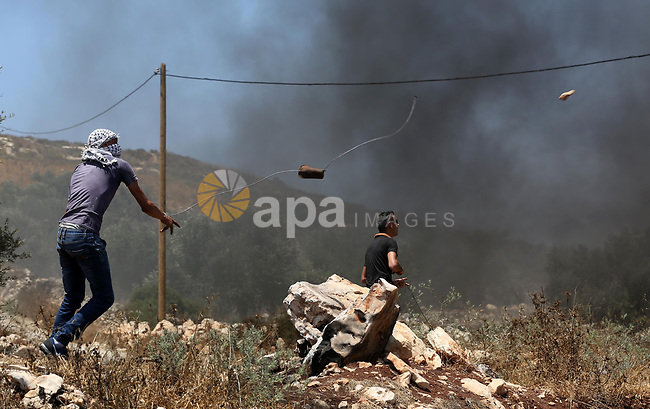 A Palestinian protester uses a slingshot to hurl stones towards Israeli security forces during clashes following a weekly demonstration against the expropriation of Palestinian land by Israel in the village of Kfar Qaddum, near Nablus, in the occupied West Bank on June 30, 2017. Photo by Ayman Ameen