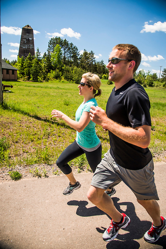 An active couple jogs runs along the Iron Ore Heritage Trail near Cliffs Shaft Mine Museum at Ishpeming, Michigan.
