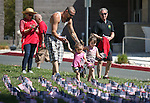 Mazzerick Nelson and his daughters Larissa, 2, and Julia, 1, place flags in the lawn of Western Nevada College as several hundred people participate in a Veterans Suicide Awareness event in Carson City, Nev., on Saturday, May 2, 2015.<br /> Photo by Cathleen Allison