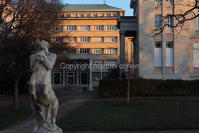 Statue of a centaur dancing and playing an autos, by Louis De Monard, 1873-1930, in the Cite Internationale Universitaire de Paris, in the 14th arrondissement of Paris, France. Behind is the Fondation Lucien Paye, designed by Jean Vernon, Bruno Philippe and Albert Laprade, 1883-1978, and inaugurated 1949, and to the right is the Fondation Hellenique, or Hellenic Foundation, designed by Nikolaos Zahos, 1875-1941, for Greek students and inaugurated in 1932. The CIUP or Cite U was founded in 1925 after the First World War by Andre Honnorat and Emile Deutsch de la Meurthe to create a place of cooperation and peace amongst students and researchers from around the world. It consists of 5,800 rooms in 40 residences, accepting another 12,000 student residents each year. Picture by Manuel Cohen. L'autorisation de reproduire cette œuvre doit etre demandee aupres de l'ADAGP/Permission to reproduce this work of art must be obtained from DACS.