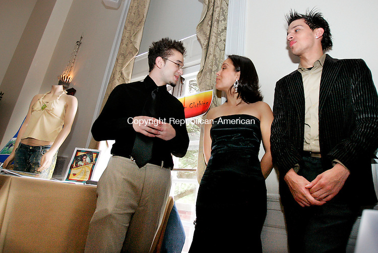 NEW HAVEN, CT. 25 May  2005--052505SV01--from left; Josh Batista,16, of Wilby High gets some help from his sister Stephanie Rentes and  friend Anthony Perez of Waterbury while competing in the state DECD's 5th annual Statewide Business Plan Competition and Business Expo for Inner-City Youth Entrepreneurship at the New Haven Lawn Club in New Haven Wednesday. Batista is a Designer of Unique &amp; Custom cloths. His sister was wearing one of his dress creations he designed and made. Steven Valenti Photo<br /> (Josh Batista,Stephanie Rentes,Anthony Perez (cq))