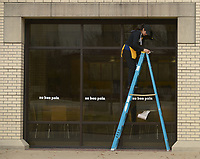 NWA Democrat-Gazette/ANDY SHUPE<br /> Cristal Hernandez, a food service worker at au bon pain, a bakery in the Arkansas Union on the University of Arkansas campus in Fayetteville, watches as a roll of paper towels falls as she cleans exterior windows Tuesday, March 20, 2018, at the shop. With the majority of students away from campus for spring break, Hernandez said that staff were busy catching up with cleaning and maintenance.