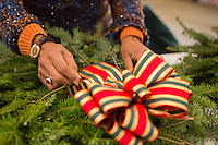 Dorothy Page of Abington attaches a bow to her wreath at the Winter in the Wissahickon event hosted by the Friends of the Wissahickon. (Dave Tavani/for NewsWorks)