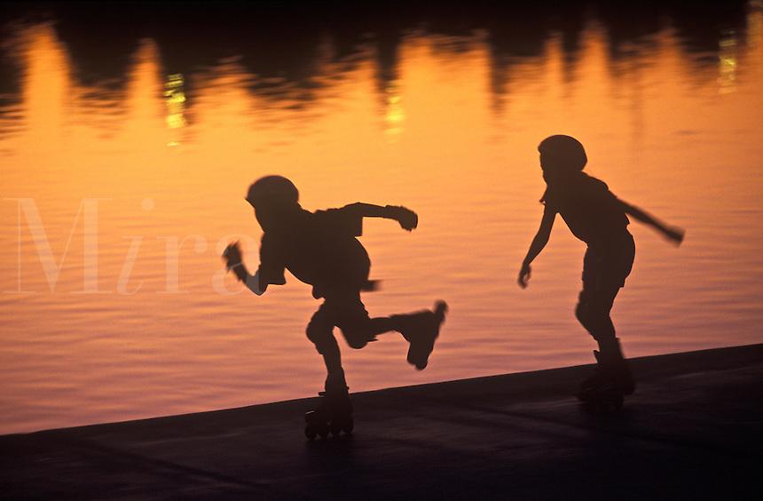 Boys rollerblading at dusk.