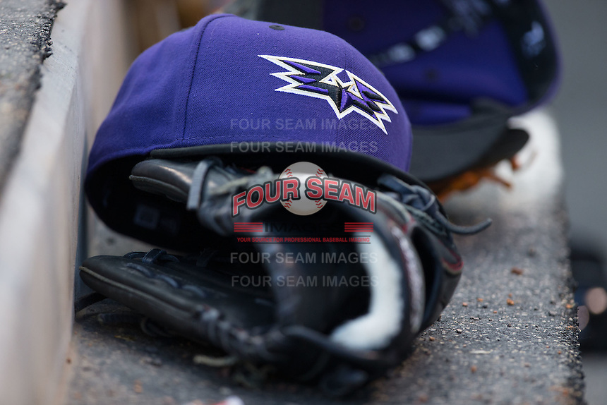 A Louisville Bats cap sits on top of a glove in the visitors dugout during the game against the Charlotte Knights at BB&T BallPark on May 12, 2015 in Charlotte, North Carolina.  The Knights defeated the Bats 4-0.  (Brian Westerholt/Four Seam Images)