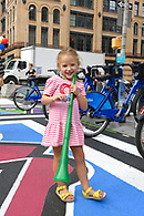 A young girl holding a colorful plastic horn which were given out at the block party.