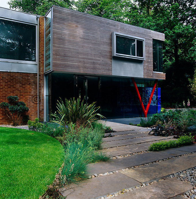 A pebble and slab stone path leads up to the glass-walled entrance to the house which is articulated by a striking red V-shaped girder
