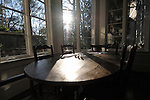 Wooden table and chairs in breakfast nook; backlit by sun through windows.