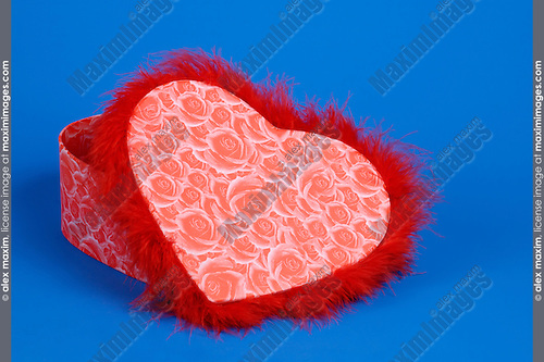 Lovely heart-shaped red fancy box isolated silhouette on blue background. Valentine's Day gift concept