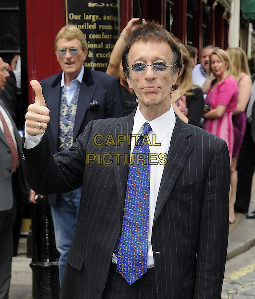 ROBIN GIBB.The Wendy Richard blue plaque unveiling, Shepherd's Tavern, London, England..July 5th, 2009.half length blue tie black pinstripe suit tinted glasses jacket hand thumb up .CAP/CAN.©Can Nguyen/Capital Pictures.