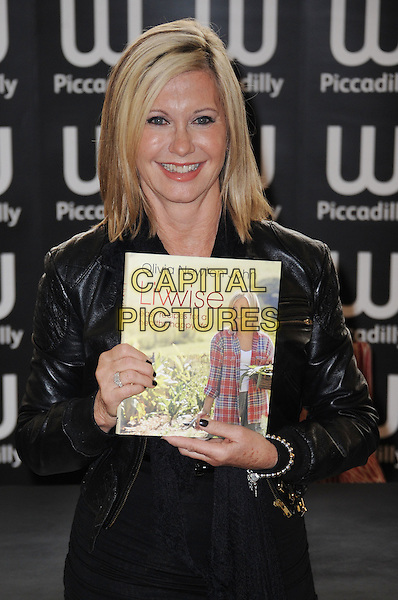 Olivia Newton-John.attended her 'Livwise: Easy Recipes For A Healthy, Happy Life' booksigning session, Waterstone's, Piccadilly, London, England..April 19th, 2012.half length black leather jacket top book.CAP/WIZ.© Wizard/Capital Pictures.
