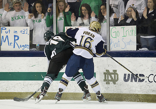 December 07, 2012:  Notre Dame right wing Michael Voran (#16) and Michigan State forward Matt DeBlouw (#19) battle for the puck along the boards during NCAA Hockey game action between the Notre Dame Fighting Irish and the Michigan State Spartans at Compton Family Ice Arena in South Bend, Indiana.  Notre Dame defeated Michigan State 3-2.