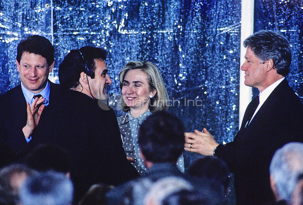 United States President Bill Clinton, right, greets performer Mandy Patinkin, left center, following a performance on the South Lawn of the White House in Washington, D.C. during a reception the evening prior to the dedication of the U.S. Holocaust Museum on April 21, 1993.  Looking on are U.S. Vice President Al Gore, left, and First lady Hillary Rodham Clinton, right center.<br /> Credit: Ron Sachs / CNP/MediaPunch