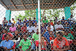 Local townspeople sit in the stands to watch the Warriors and other baseball players perform in a showcase for Major League Baseball scouts on Friday, February 26, 2010 in San Antonio de Guerra, Dominican Republic.