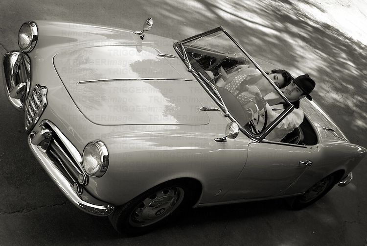 A young couple in an Italian sports car