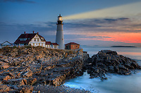 The Portland Head Lighthouse shines brightly as color begins to appear in the eastern sky shortly before sunrise. The lighthouse, built in 1791 to protect mariners entering Casco Bay, is located in Fort Williams Park, Cape Elizabeth, Maine.