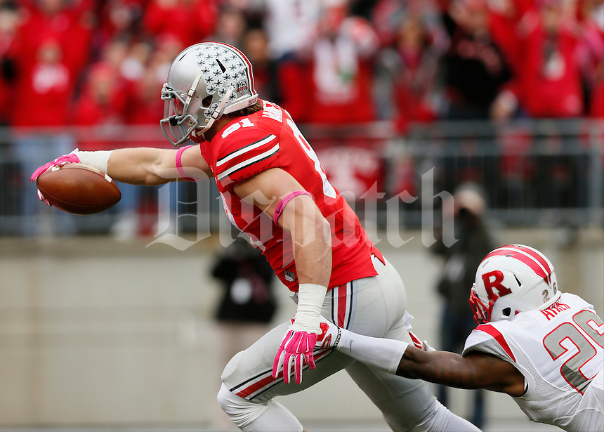 Ohio State Buckeyes tight end Nick Vannett (81) stretched for a touchdown while being tackled by Rutgers Scarlet Knights defensive back Johnathan Aiken (26) during Saturday's NCAA Division I football game at Ohio Stadium in Columbus. The Buckeyes led at halftime 35-7. (Dispatch Photo by Barbara J. Perenic)