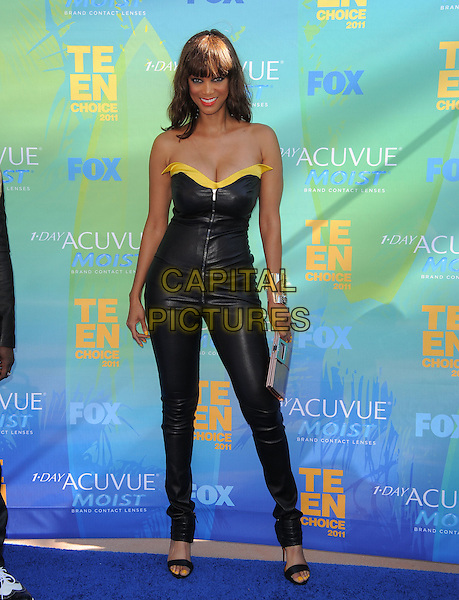 Tyra Banks.The Fox 2011 Teen Choice Awards held at Gibson Ampitheatre in Universal City, California, USA..August 7th, 2010                    .full length leather catsuit jumpsuit silver bracelet jewellery jewelry yellow  bronze metallic clutch bag.CAP/RKE/DVS.©DVS/RockinExposures/Capital Pictures.