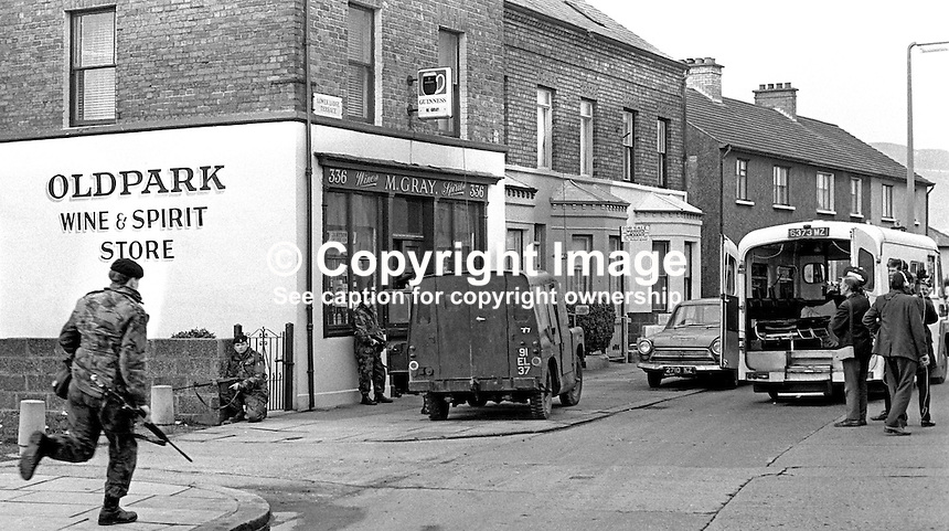 Army, police and ambulance crew at scene of incident in which two policemen were shot dead on 11th November 1971 by the Provisional IRA in an off-licence only 100 yards from Oldpark RUC Station in North Belfast. The police victims were later named as Constable Walter Moore, Londonderry, and Sergeant Dermot Hurley, originally from Wicklow in the Rep of Ireland. Sgt Hurley, a fluent Irish speaker, was the first Roman Catholic member of the RUC to be murdered in the Troubles. 19711110447d.<br />