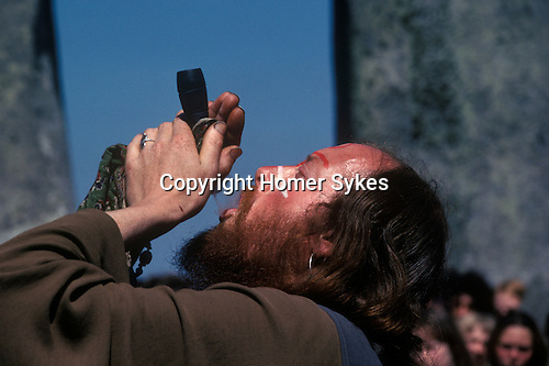 "Sid Rawle known as the King of the Hippies. 1970's style hippies attend the first free festival at Stonehenge to celebrate the summer solstice June 21st 1970's.Smoking a ""Peace Pipe""."