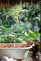 A guest relaxes in an outdoor bath on a secluded deck