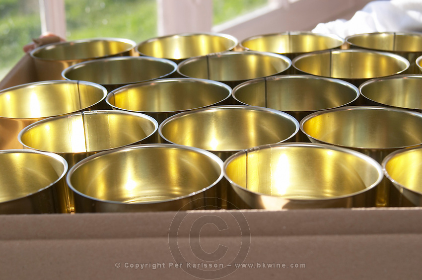 How to make foie gras duck's liver (series of images): Metal conserve tins cans on a tray that will be filled with duck liver. Ferme de Biorne duck and fowl farm Dordogne France Workshop on how to make foie gras duck liver pate and other conserves