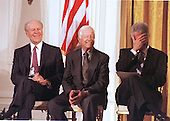 United States President Bill Clinton, right, covers his face as he laughs along with former U.S. President Gerald R. Ford, left, and former U.S. President Jimmy Carter as a reaction to a comment by former Secretary of State Henry Kissinger, not shown, during an event featuring a bipartisan group of distinguished Americans, highlighting their support for permanent normal trade relations (PNTR) with China, at the White House, May 9, 2000. <br /> Credit: Ron Sachs / CNP<br /> Credit: Ron Sachs / CNP