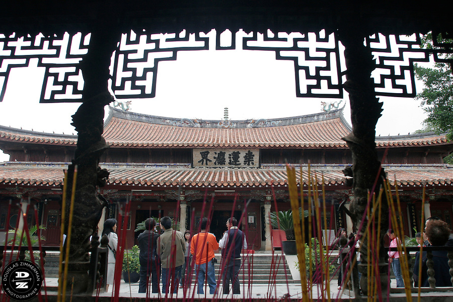 Tourist view the Grand Buddha Hall of the Kaiyuan Temple in Quanzhou, China.  The temple dates back to 686 AD, and is distinguished by its pair of two five-story pagodas.  Photograph by Douglas ZImmerman