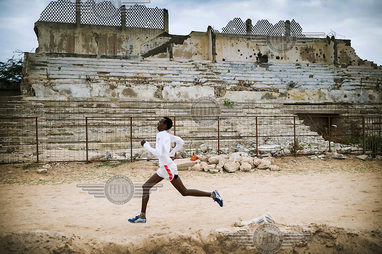 An athlete trains in a partially destroyed sports stadium.