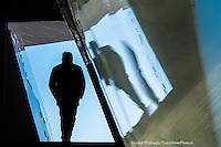 Nederland, Amsterdam, 17 jan 2016<br /> Man loopt door een doorgang van het Eye filmmuseum en wordt gespiegeld in een glazen balustrade.  <br />  <br /> Foto: (c) Michiel Wijnbergh
