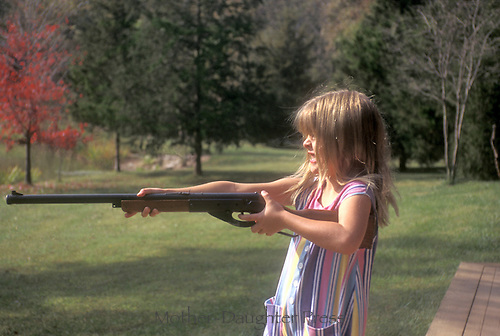 Fierce young girl holding BB gun takes  aim