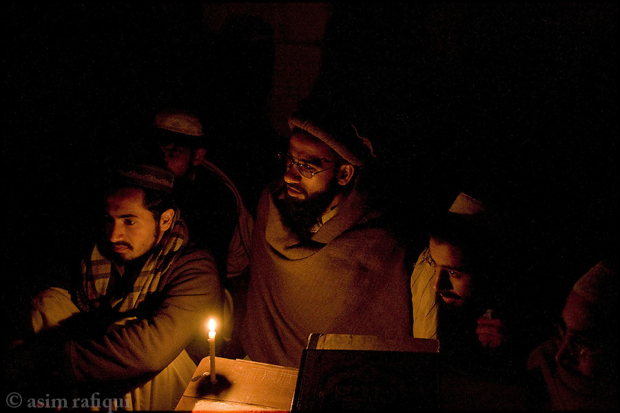 in the dark of a power outage, madrassa student discuss the koran in a study group at the darol-uloom sarhad madrassa in peshawar