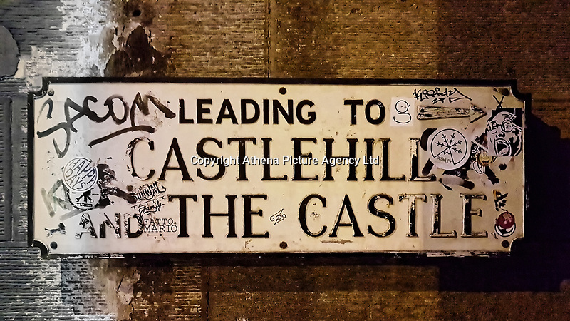 Pictured: A sign to Castlehill and The Castle with various graffitis, slogans and stickers.<br /> Re: Edinburgh, Scotland, UK. 06 April 2018