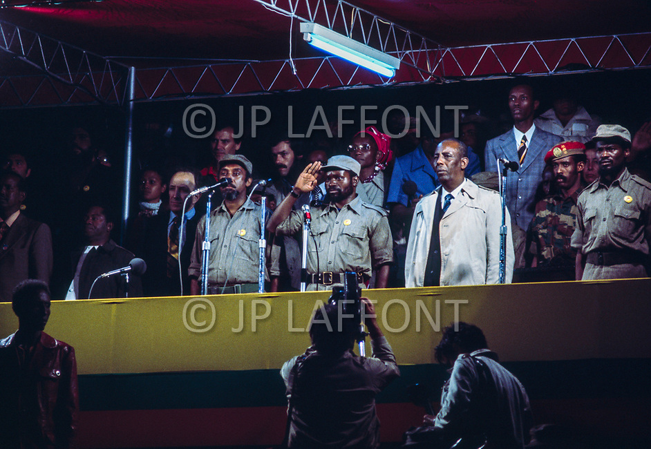 25 Jun 1975, Mozambique --- Speech of Samora Machel (saluting), commander-in-chief of the Front for the Liberation of Mozambique (FRELIMO) stands with Marcelino dos Santos (to his left) the night of Mozambique's Independence. Machel is the first president of newly independent Mozambique, and Marcelino dos Santos, the vice-president. | Location: Lourenco Marques, Mozambique. --- Image by © JP Laffont