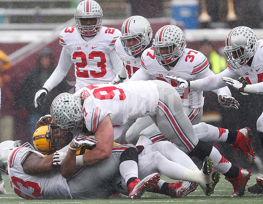 Ohio State Buckeyes defensive lineman Joey Bosa (97) and Ohio State Buckeyes defensive tackle Michael Bennett (63) overwhelm Minnesota Golden Gophers running back David Cobb (27) in the second quarter of the college football game between the Ohio State Buckeyes and the Minnesota Golden Gophers at TCF Bank Stadium in Minneapolis, Saturday morning, November 15, 2014. As of half time the Ohio State Buckeyes led the Minnesota Golden Gophers 17 - 14. (The Columbus Dispatch / Eamon Queeney)