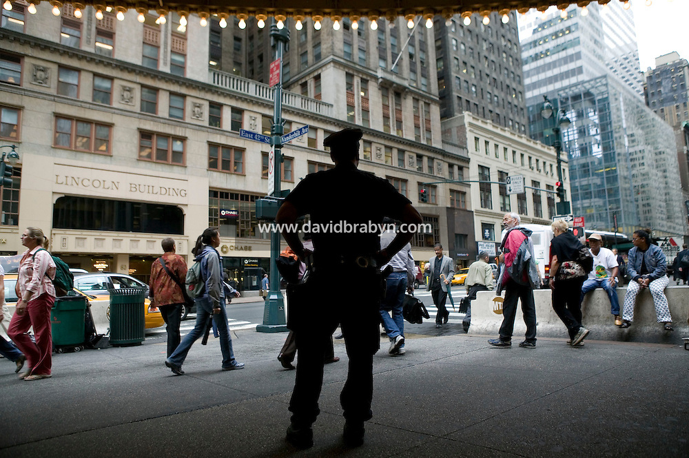 7 October 2005 - New York City, NY - New York City police officer Martinez (first name withheld, foreground) stands guard at the entrance to Grand Central Station in New York City, on 7 October 2005, the day after the Police Department announced a specific terrorist threat to the subway system had been identified. Photo Credit: David Brabyn.