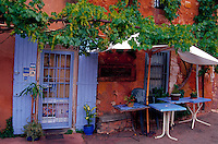 A scenic Frence sidewalk cafe with blue shutters and vines. Rousillon, France.